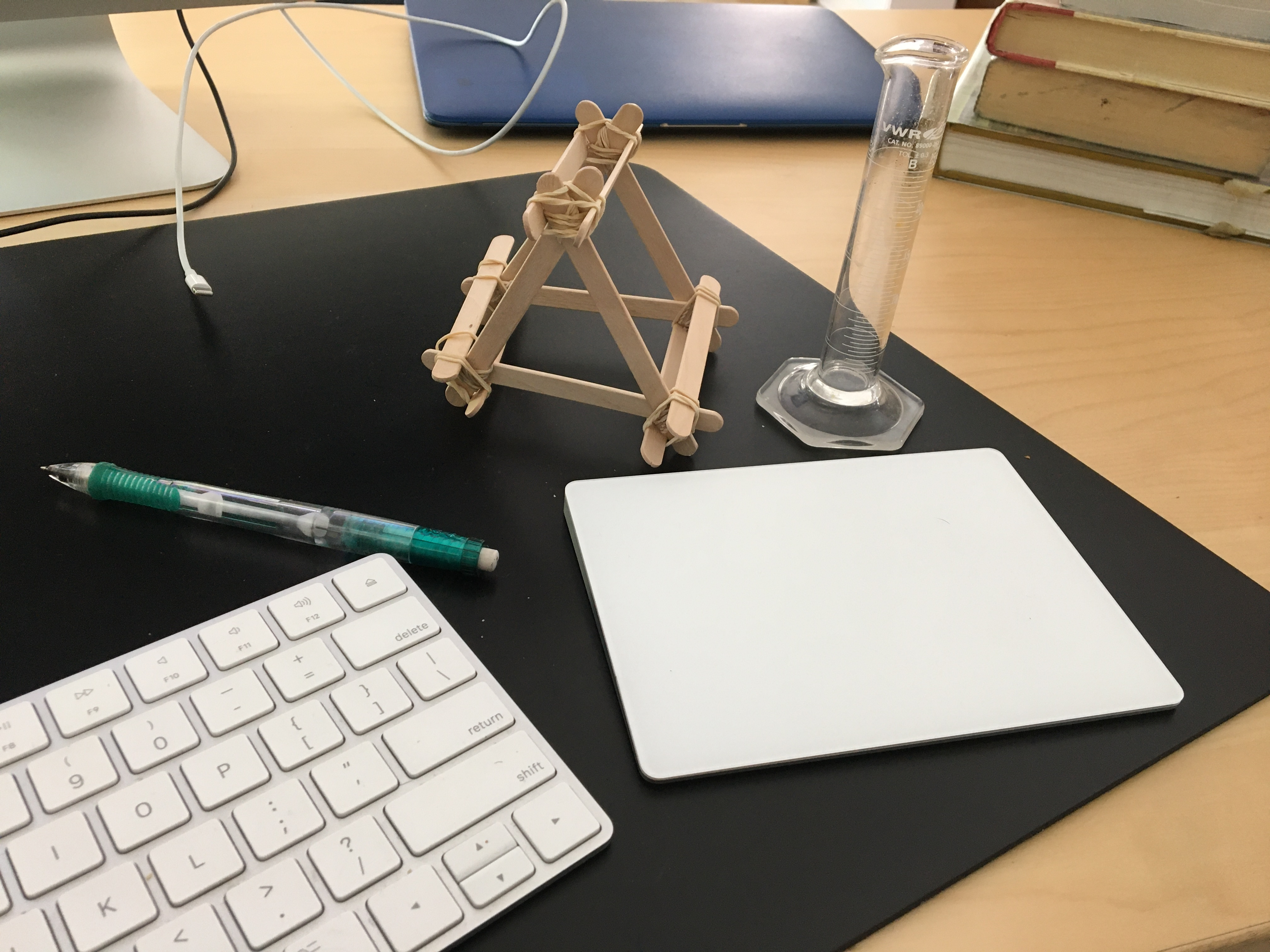 Photo of teacher's desk, with beaker and popsicle stick contraption